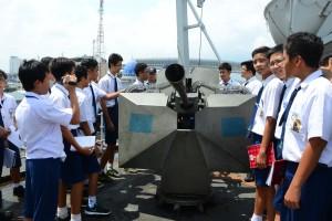 Siswa–siswi SMP Candle Tree School sedang mencoba memegang senjata meriam milik KRI Tanjung Nusanive 973. (Foto: Dispen Kolinlamil)