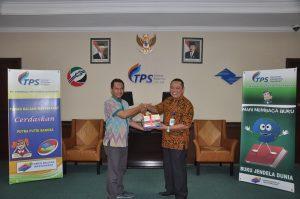 Direktur Utama PT. Terminal Petikemas Surabaya, Yon Irawan (kiri) secara simbolik menyerahkan bantuan 357 buku kepada Taman Bacaan Masyarakat yang diterima oleh Kepala Bidang Pelayanan Dinas Perpustakaan dan Kearsipan Kota Surabaya, Chairul Anwar  (kanan) di Gedung Administrasi PT. TPS, Jum'at (25/8).